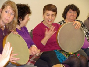 Women learning to play frame drums